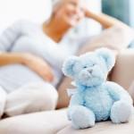 Happy pregnant female with teddy bear