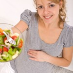 Pregnant woman holding a bowl of salad