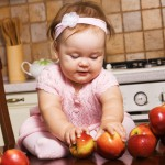 Cute infant girl playing at kitchen